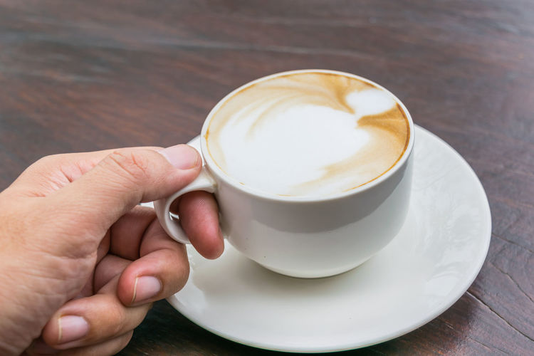 High angle view of hand holding coffee cup on table