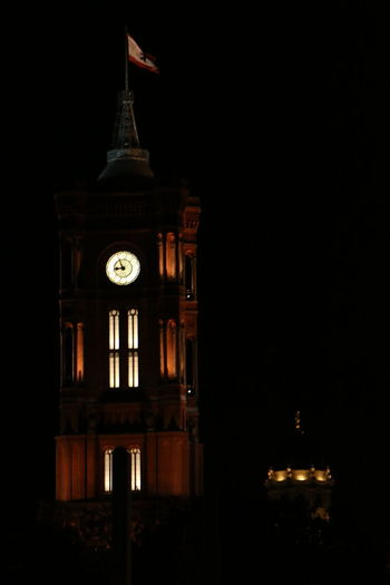 Illuminated clock tower in city at night