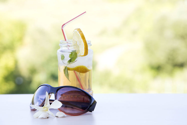 Close-up of sunglasses and drink on table