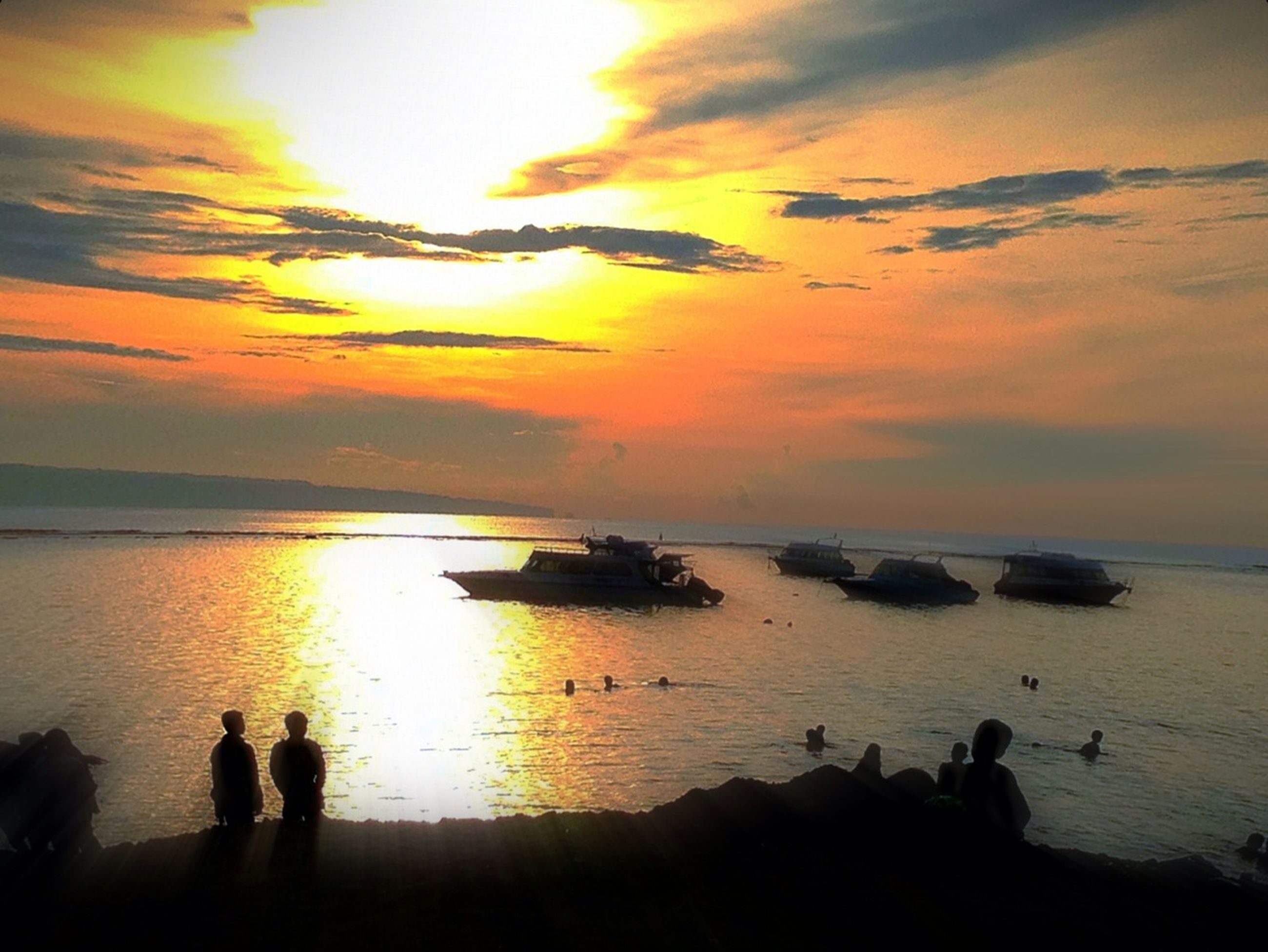 sunset, sea, water, horizon over water, silhouette, scenics, beach, beauty in nature, sky, sun, tranquil scene, tranquility, orange color, shore, reflection, idyllic, nature, leisure activity, medium group of people