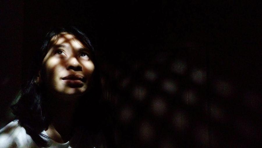 Woman looking up against wall in darkroom
