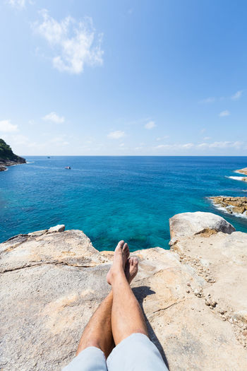 Low Section Of Man Relaxing On Rock By Sea Against Sky During Sunny Day