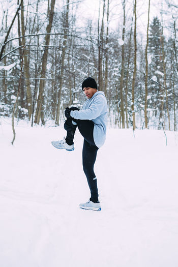 Man Exercising On Snow Covered Field