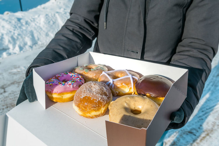 Midsection of woman holding fresh donuts in cardboard box during winter