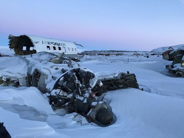 Snow covered damaged airplane against sky
