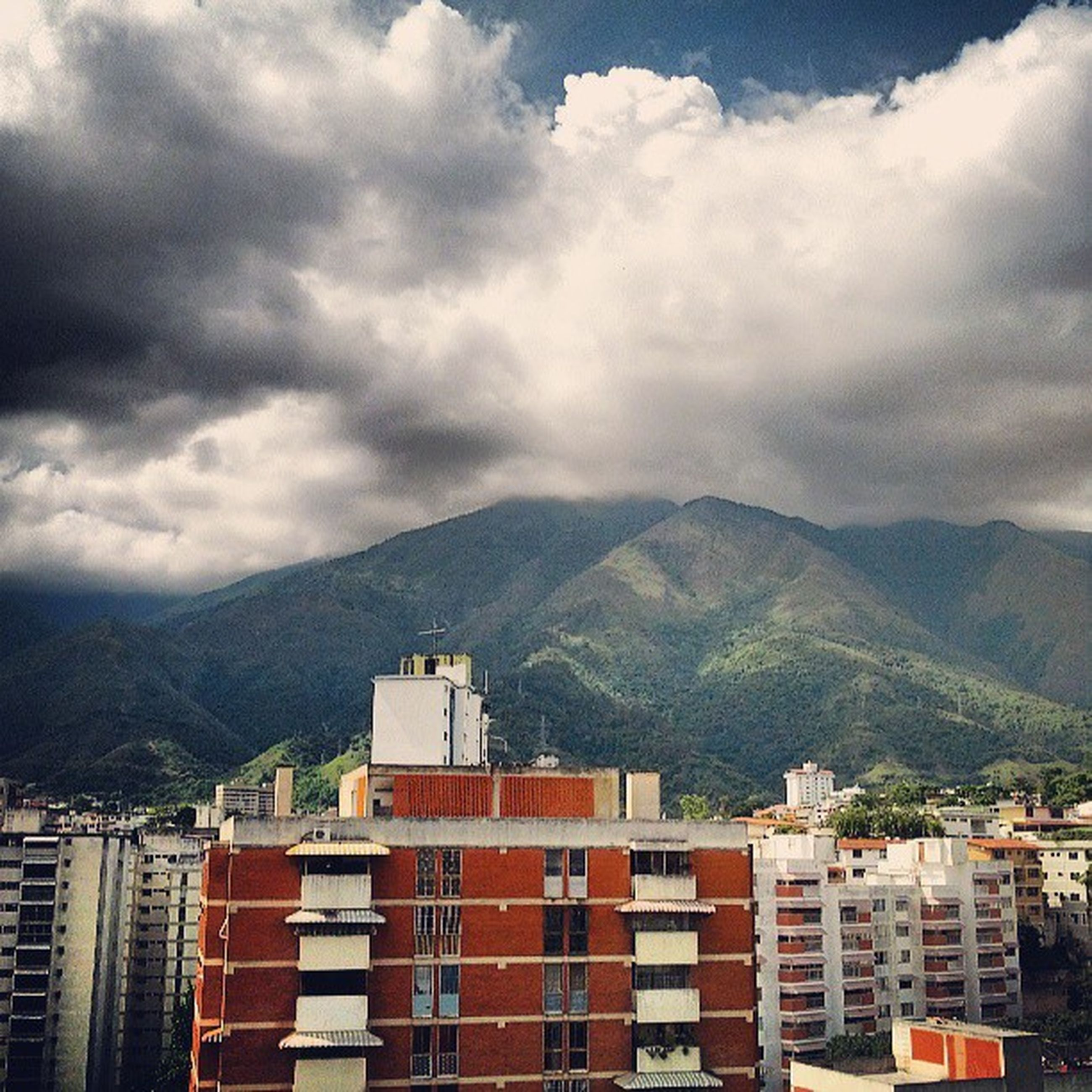 mountain, mountain range, building exterior, sky, architecture, built structure, cloud - sky, cloudy, cloud, house, scenics, residential structure, nature, day, residential building, beauty in nature, weather, overcast, outdoors, no people