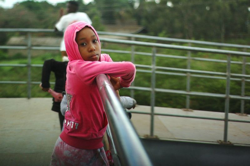 Side view portrait of girl leaning on railing