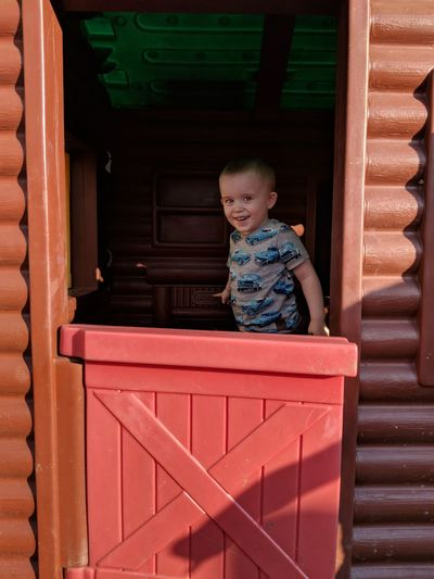 Portrait of boy smiling while standing house entrance