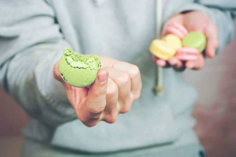 Holding Food And Drink Food Midsection Human Hand One Person Hand Human Body Part Focus On Foreground Close-up Front View Adult Healthy Eating Showing Freshness Wellbeing Casual Clothing Men Green Color Temptation Macaroon