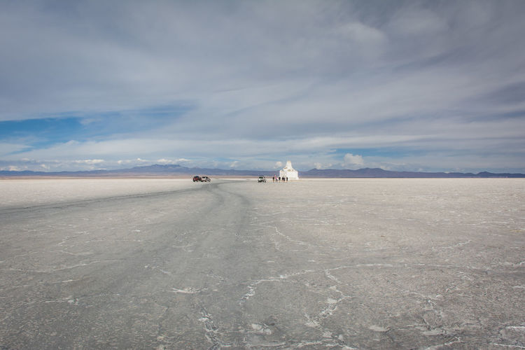 Distant Group Of Tourists On Bolivian Salt Flat