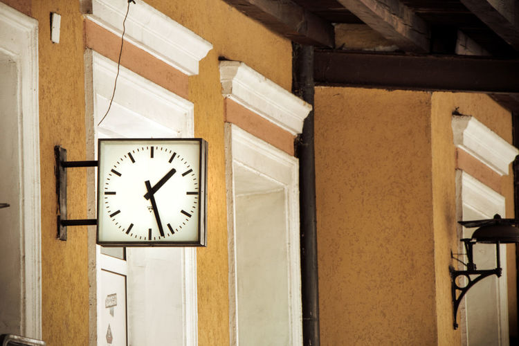 Low angle view of clock on wall in building