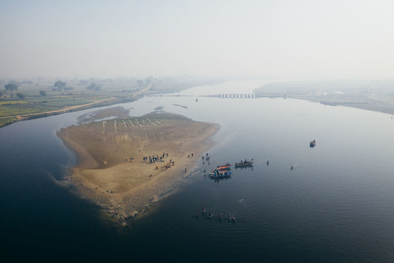 Groups of people bath along the Yamuna River in Mathura, India. Water Sea Nature High Angle View Day Scenics - Nature Transportation Beauty In Nature Aerial View Sky Nautical Vessel No People Tranquility Waterfront Land Architecture Outdoors Beach Coastline India Week On Eyeem Mathura Hindu Dronephotography Mavic Pro 2 Mavic 2 Pro Dji Travel Culture