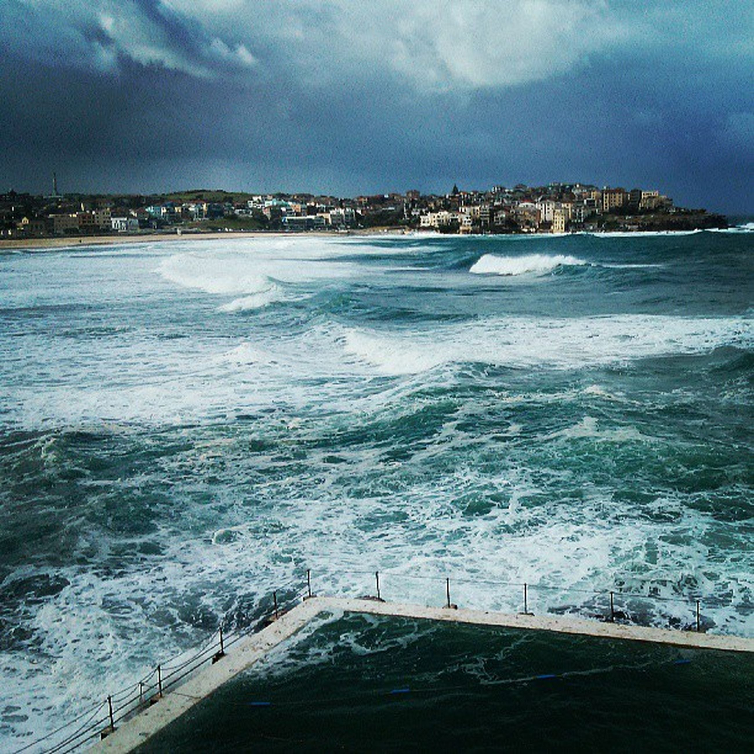water, sea, sky, wave, building exterior, cloud - sky, surf, architecture, built structure, beach, scenics, beauty in nature, nature, blue, cloudy, shore, cloud, coastline, waterfront, motion