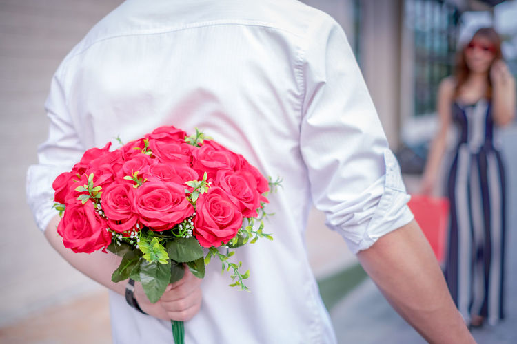 Midsection Of Man Holding Bouquet While Walking Towards Girlfriend On Footpath