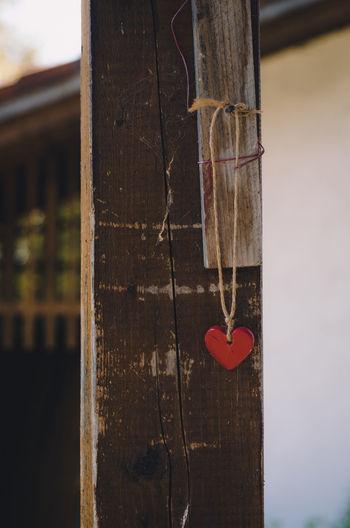 Close-up of heart shape hanging on metal door