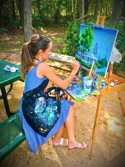 Full Length Of Smiling Woman Painting While Sitting On Bench