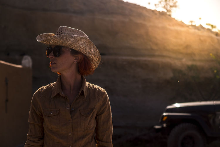 Young Woman Wearing Sunglasses And Hat Looking Away While Standing Against Mountain During Sunset