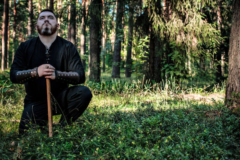 Man with axe crouching on field against trees