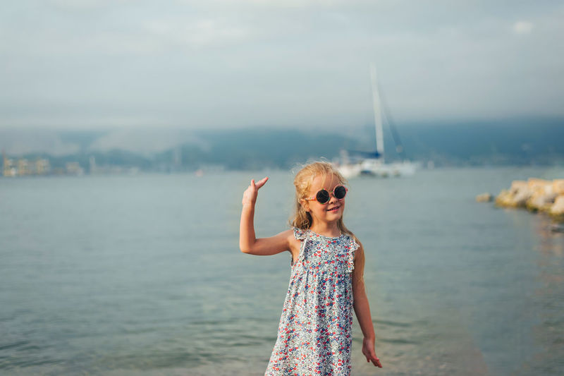 Little girl with long blonde hair stands with her back on the seashore in summer