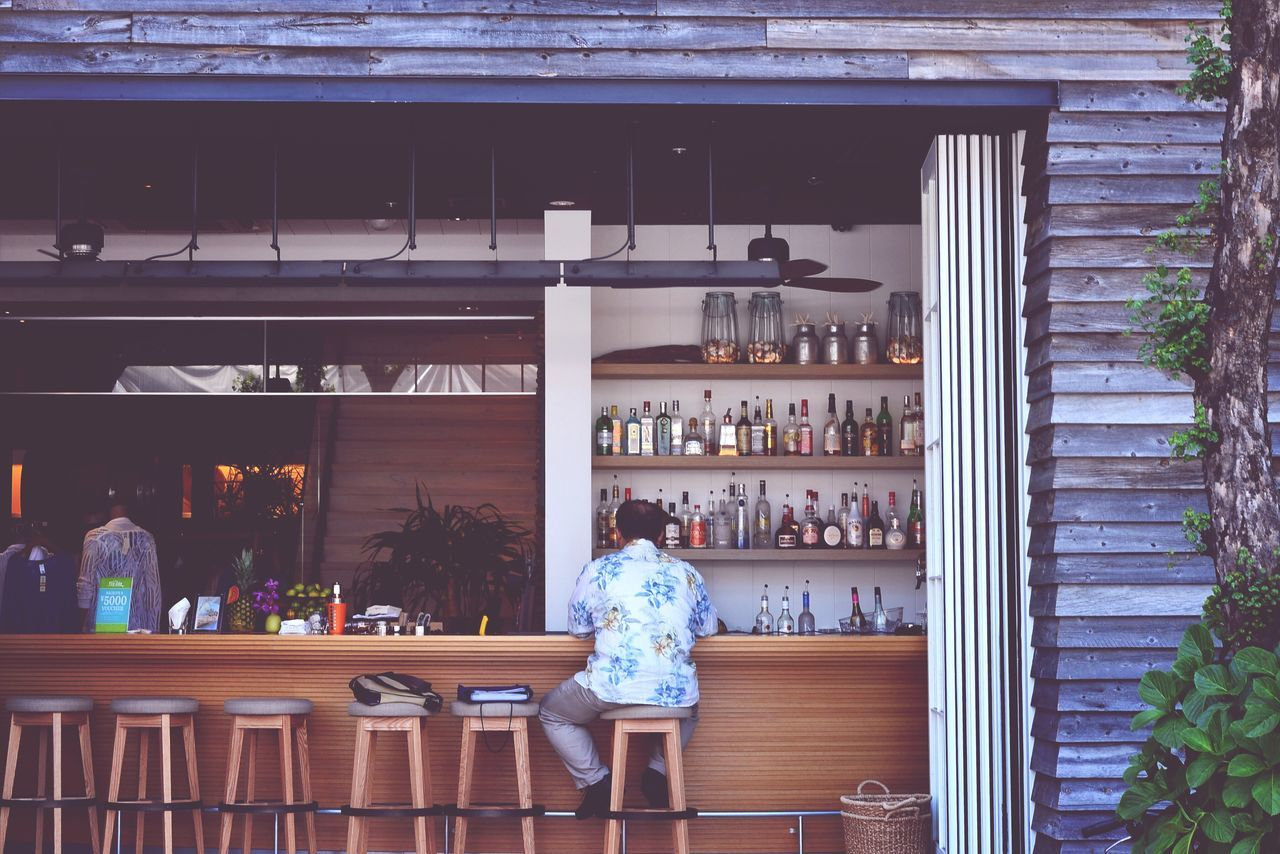 Rear view of man sitting at bar counter