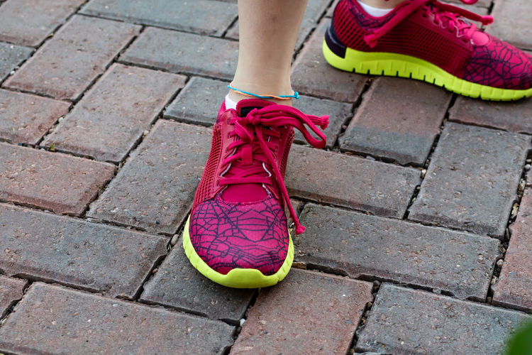 Body Part Day Fashion Footpath High Angle View Human Body Part Human Foot Human Leg Human Limb Lifestyles Limb Low Section One Person Outdoors Paving Stone Pink Color Red Shoe Sock Sport Street Women