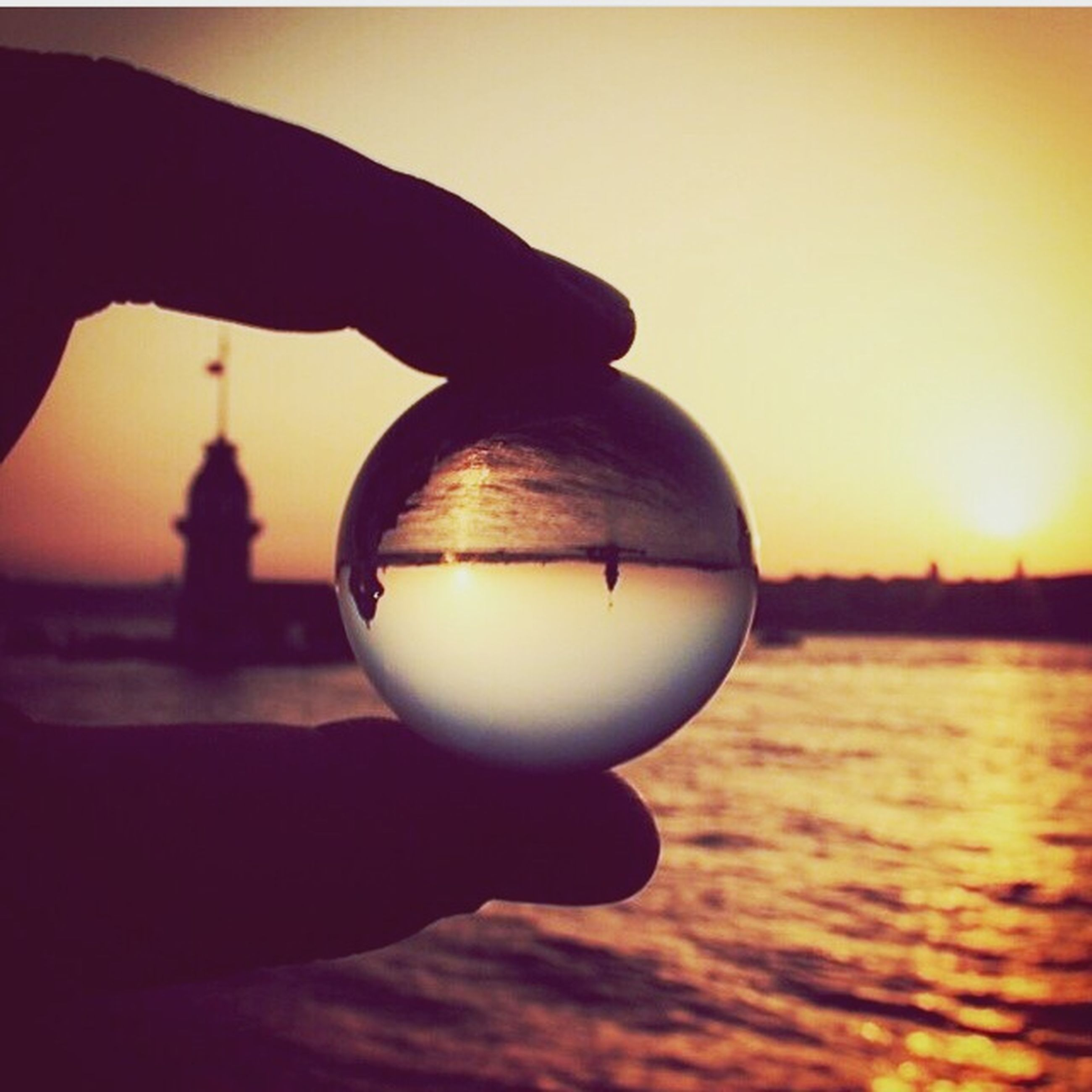 sunset, water, sky, orange color, sphere, focus on foreground, reflection, holding, sun, person, close-up, silhouette, sea, clear sky, dusk, outdoors, built structure, nature