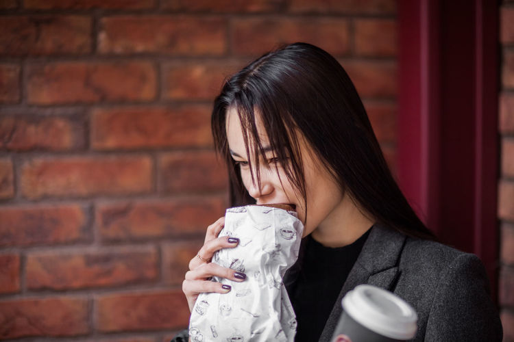 Woman eating food against brick wall