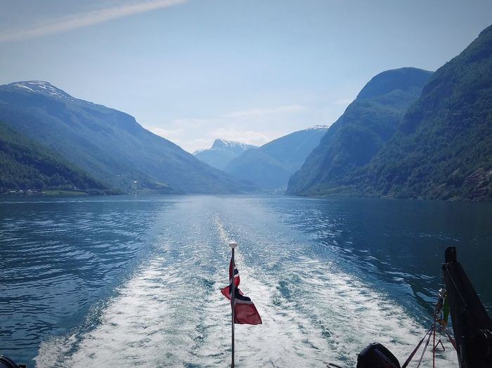 Norwegian flag waving in the wake of a fjord boat with a panoramic view of sognefjord.