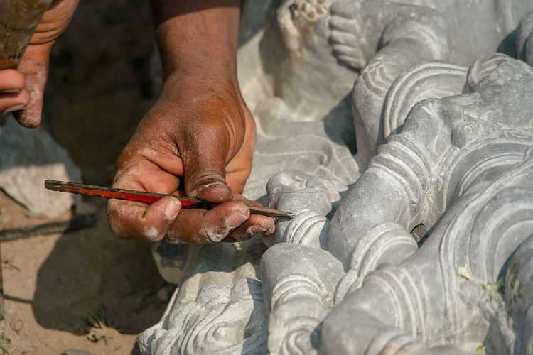 Cropped hands of man working on sculpture