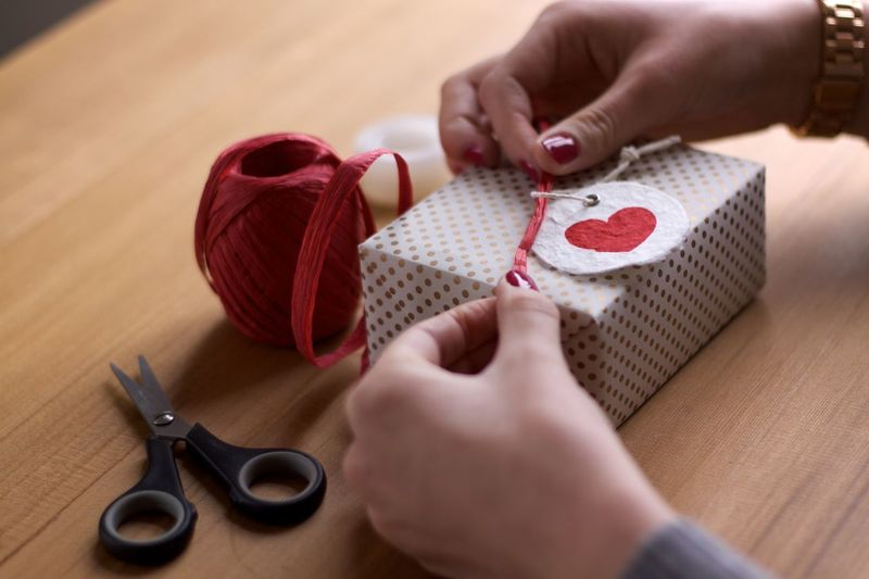 Cropped hands tying label on gift box