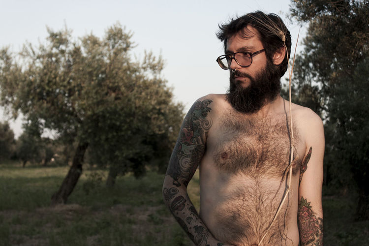 Shirtless Man Standing On Grassy Field
