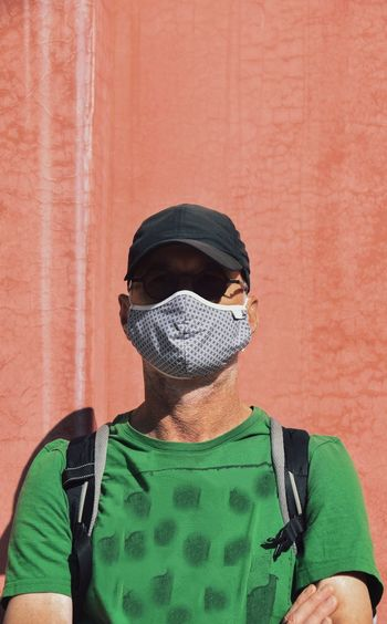 Portrait of man wearing mask standing against wall