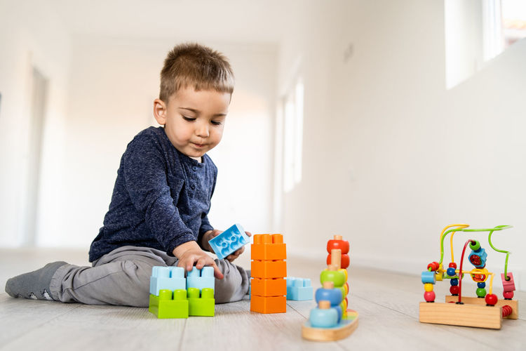 Childhood Child Toy One Person Males  Indoors  Men Multi Colored Toy Block Boys Home Interior Leisure Activity Real People Lifestyles Baby Cute Playing Casual Clothing Innocence Development Flooring