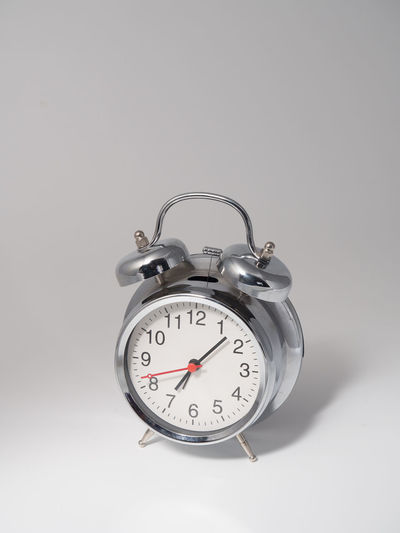 Clock Alarm Clock Studio Shot Time Indoors  Still Life Number No People Single Object Close-up Copy Space Accuracy White Background Gray Cut Out Table Metal Minute Hand