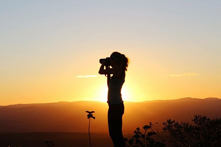 Silhouette of woman photographing at sunset