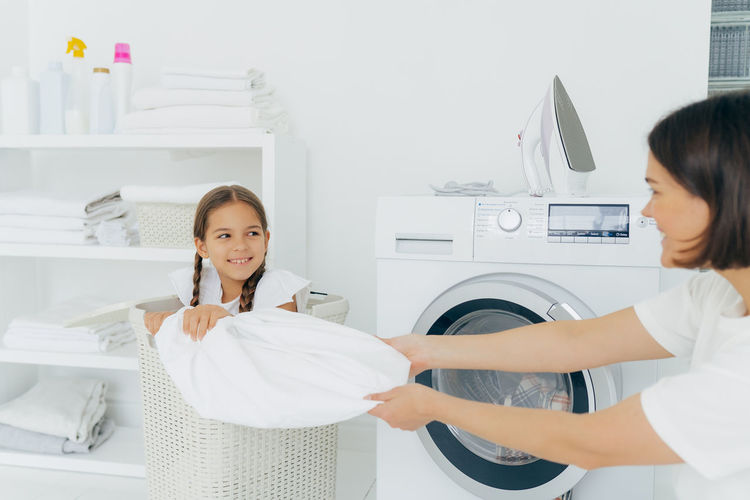 Playful mother with daughter doing laundry at home