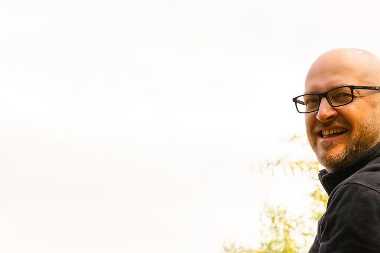 Portrait of man wearing eyeglasses against clear sky