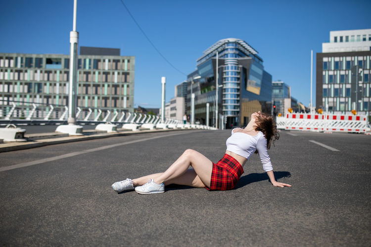 Young woman on road against sky in city