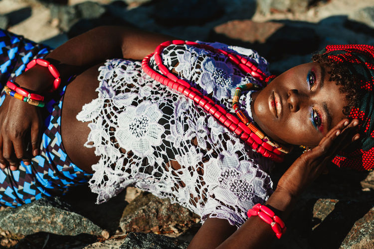 Portrait Of Young Woman Lying On Rocks