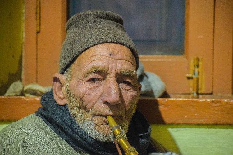 Portrait of senior man smoking hookah