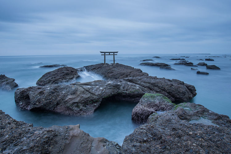 Torii Gate On Rock In Sea Against Cloudy Sky