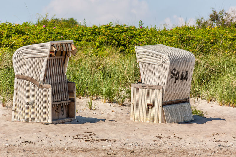 Hooded beach chairs by grass on sunny day