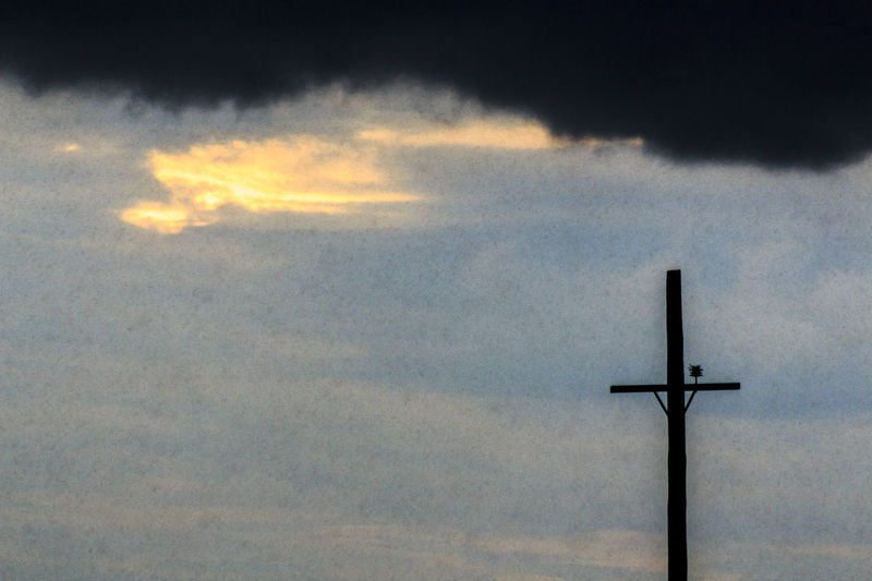 Low angle view of silhouette cross against sky during sunset