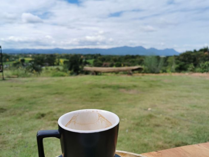 Coffee cup on field against sky