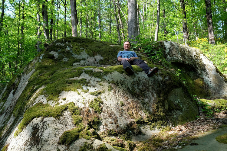 Portrait of man sitting on rock at forest