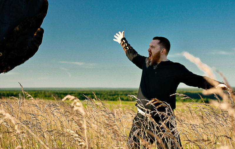 Hunter Screaming While Standing On Grassy Field Against Sky
