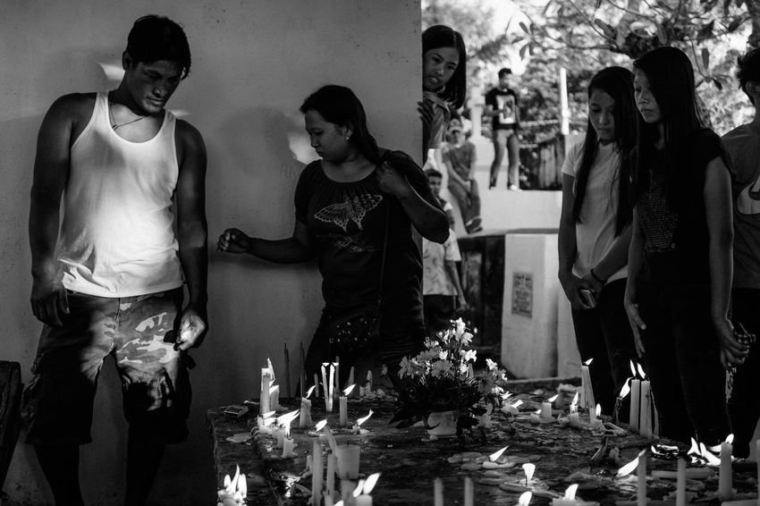 Families light candles, brought flowers and offered prayers at the graves of their dear departed during the observance of All Saints Day on Nov. 1, 2016 at Alaminos City Public Cemetery in the Philippines. During this day, millions across the Philippines visit cemeteries to pay their respects to their dead, in an annual tradition that combines Catholic religious rites with the country's penchant for festivity. People The Human Condition Tradition Culture Philippines Photojournalism Light And Shadow Real People Eyeem Philippines Blackandwhite B&w People And PlacesEverybodystreet The Photojournalist - 2017 EyeEm Awards Day Of The Dead All Souls Day Chiaroscuro  The Street Photographer - 2017 EyeEm Awards Black And White Friday