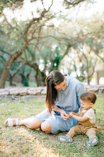 Mother and daughter sitting on grass in park