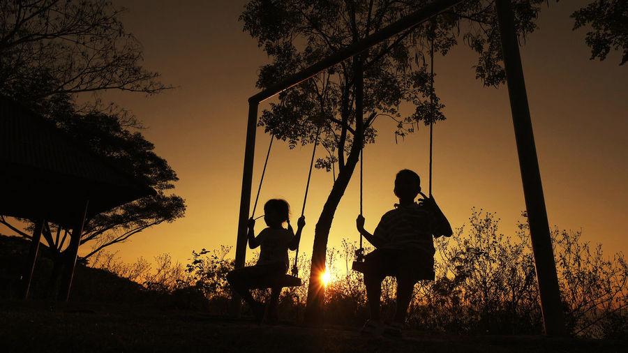 Silhouette children on swing during sunset