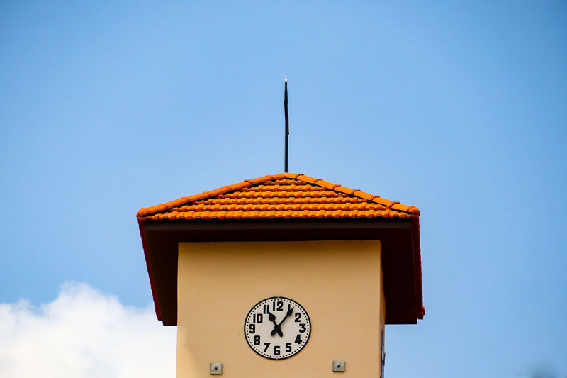 Low angle view of clock on building against clear sky